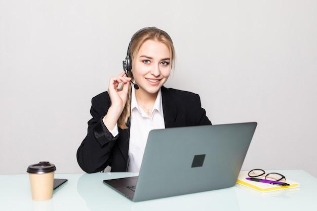 Portret van een glimlachende onderneemster met een hoofdtelefoon bij het werken in een call centre in bureau Gratis Foto