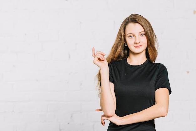 Portret van een glimlachende tiener die zich tegen witte muur bevindt Gratis Foto