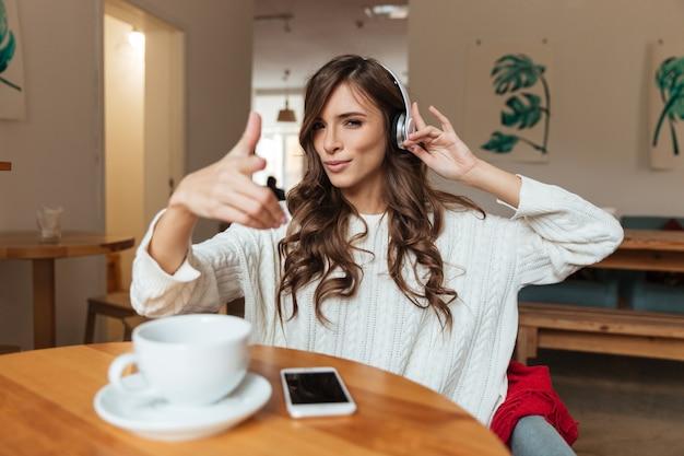 Portret van een glimlachende vrouw die aan muziek luistert Gratis Foto