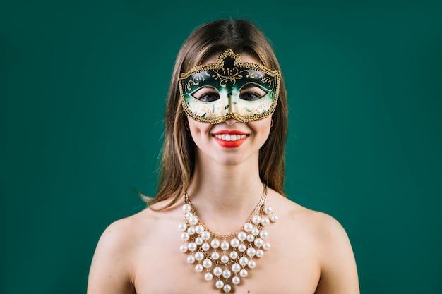 Portret van een glimlachende vrouw die carnaval-masker op gekleurde achtergrond draagt Gratis Foto