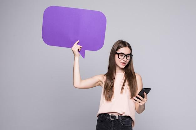 Portret van een glimlachende vrouw die lege toespraakbel toont en mobiele telefoon houdt die over grijze muur wordt geïsoleerd Gratis Foto