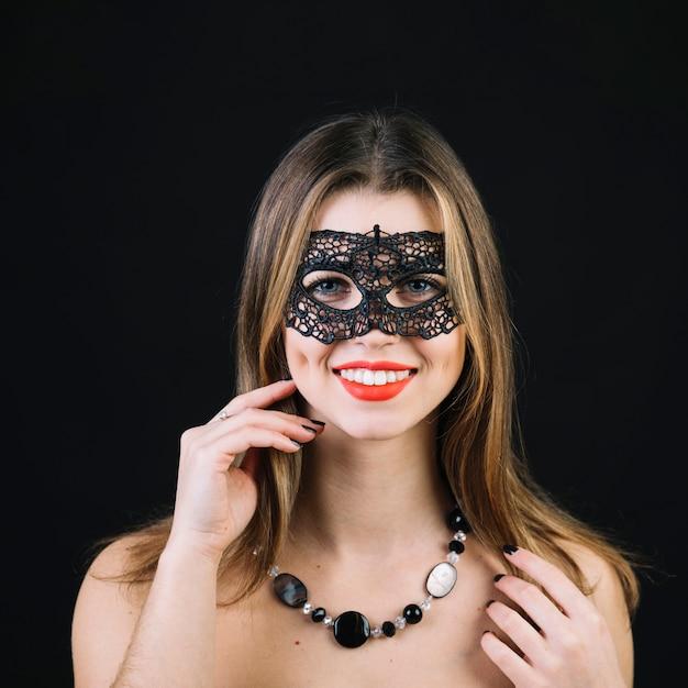 Portret van een glimlachende vrouw in carnaval-masker die halsband op zwarte achtergrond dragen Gratis Foto