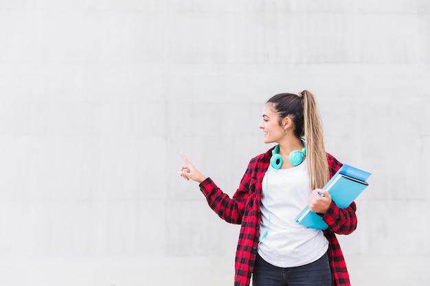 Portret van een glimlachende vrouwelijke universiteitsstudentholding boeken die in hand haar vinger op witte muur met exemplaarruimte richten Gratis Foto
