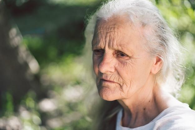 Portret van een grijsharige volwassen grootmoeder tegen de achtergrond van de natuur Premium Foto