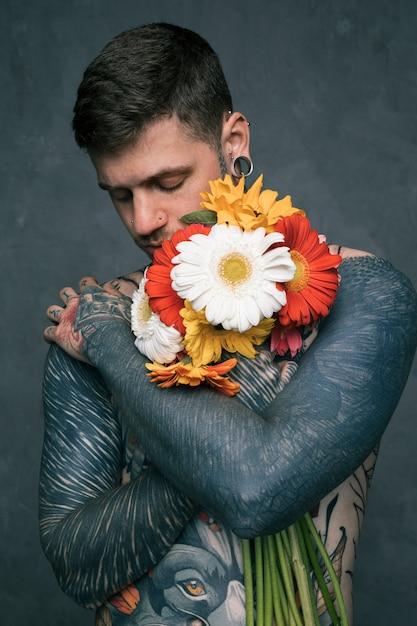 Portret van een hipster jonge man met getatoeëerd op zijn lichaam omarmen de gerbera bloemen Gratis Foto