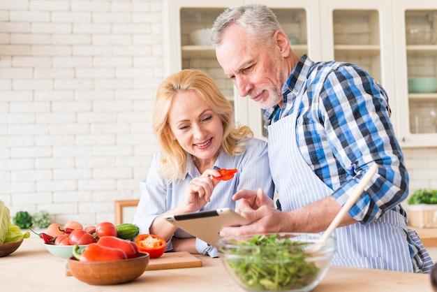 Portret van een hoger paar die digitale tablet bekijken terwijl het voorbereiden van de salade in de keuken Gratis Foto