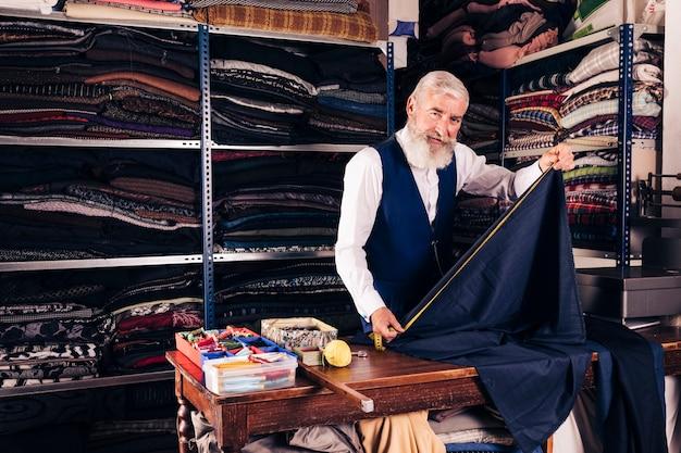 Portret van een hogere mannelijke kleermaker die meting van blauwe stof met metende band op lijst in zijn winkel neemt Gratis Foto