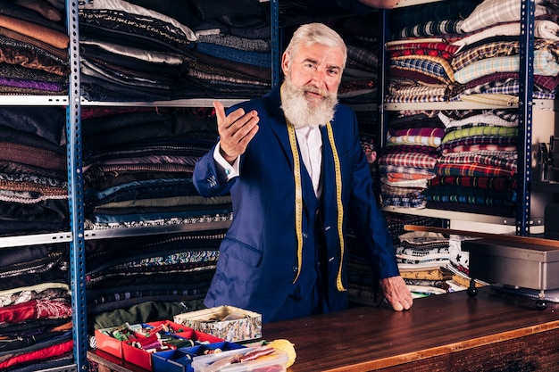 Portret van een hogere mannelijke manierontwerper die iemand in zijn winkel uitnodigen Gratis Foto