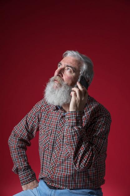 Portret van een hogere mens die op mobiele telefoon spreekt die omhoog tegen rode achtergrond kijkt Gratis Foto