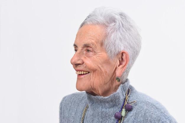 Portret van een hogere vrouw die op witte achtergrond glimlacht Premium Foto