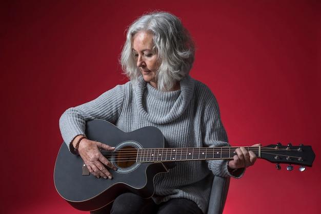Portret van een hogere vrouwenzitting op stoel die de gitaar spelen tegen rode achtergrond Gratis Foto
