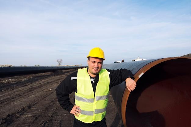 Portret van een industriële arbeider die zich door gasleiding bij bouwplaats bevindt Gratis Foto