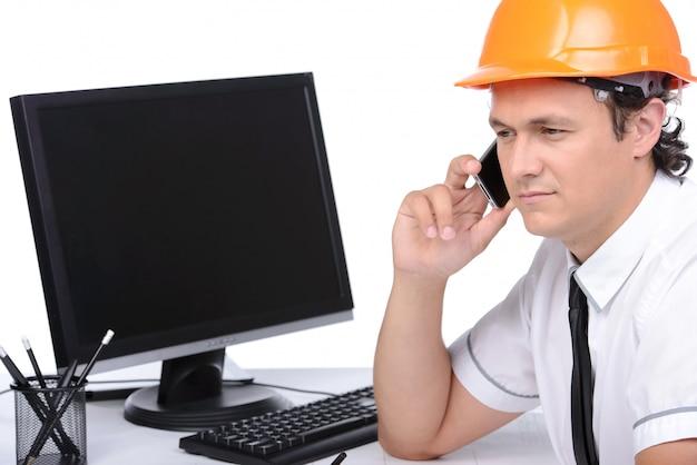 Portret van een ingenieur die een pc gebruikt en aan de telefoon spreekt. Premium Foto