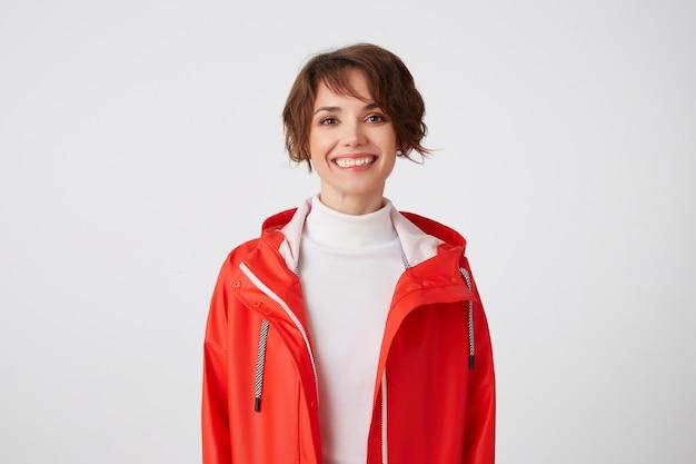 Portret van een jong breed glimlachend schattig korthaar meisje gekleed in witte golf en rode regenjas, op zoek met een gelukkige uitdrukking, staande. Gratis Foto