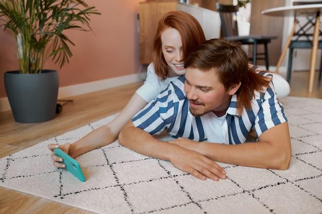 Portret van een jong echtpaar dat rust thuis heeft Premium Foto