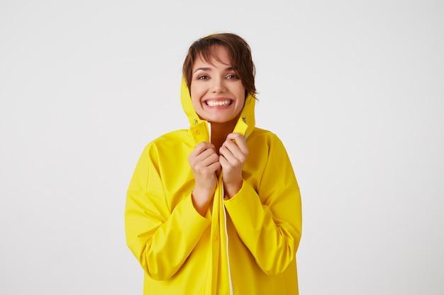 Portret van een jong gelukkig schattig korthaar meisje draagt in gele regenjas, verstopt onder een regenkap, glimlacht breed en kijkt naar de camera, staat over witte muur. Gratis Foto