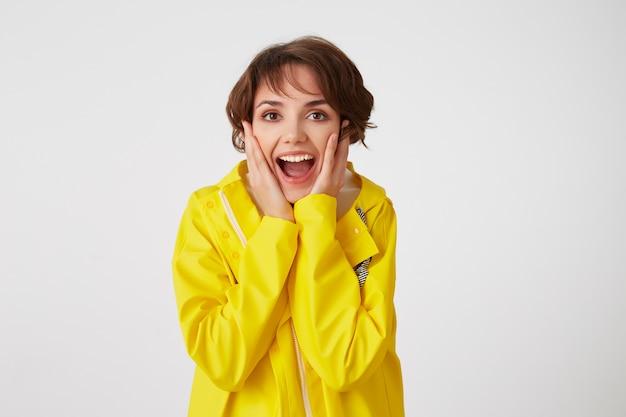 Portret van een jong gelukkig verbaasd schattig korthaar meisje draagt in gele regenjas, met wijd open mond en ogen, raakt wangen, staat over witte muur. Gratis Foto