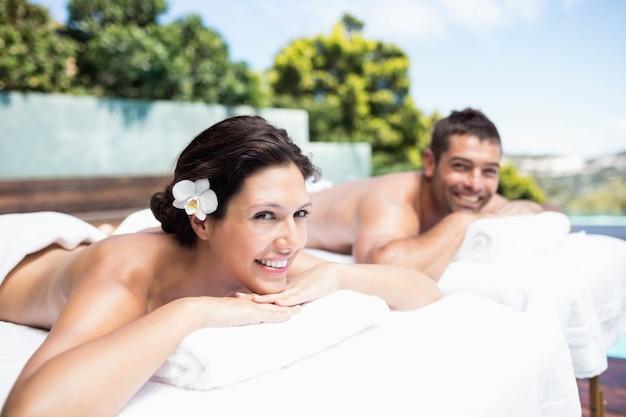 Portret van een jong koppel glimlachend en ontspannen op massage tafel in spa Premium Foto
