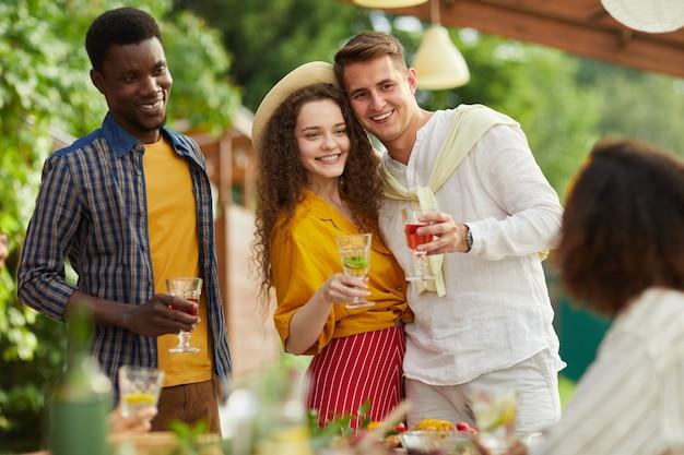 Portret van een jong koppel omarmen terwijl staande aan tafel en genieten van een diner met vrienden buiten op zomerfeest Premium Foto