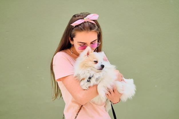 Portret van een jong meisje dat met een witte pluizige pomeranian loopt. Premium Foto