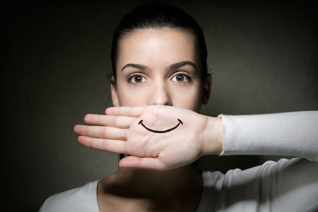 Portret van een jong meisje dat met haar hand huilt en haar mond bedekt Gratis Foto