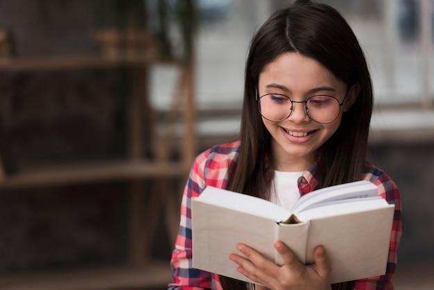 Portret van een jong meisje het lezen van een boek Gratis Foto