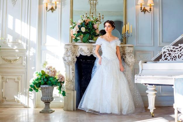 Portret van een jong meisje in een mooie jurk in het interieur, vrouwelijke schoonheid Premium Foto