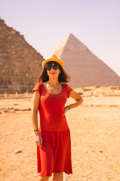 Portret van een jong meisje in rode jurk bij de piramide van cheops de grootste piramide. de piramides van gizeh zijn het oudste grafmonument ter wereld. in de stad caïro, egypte Premium Foto