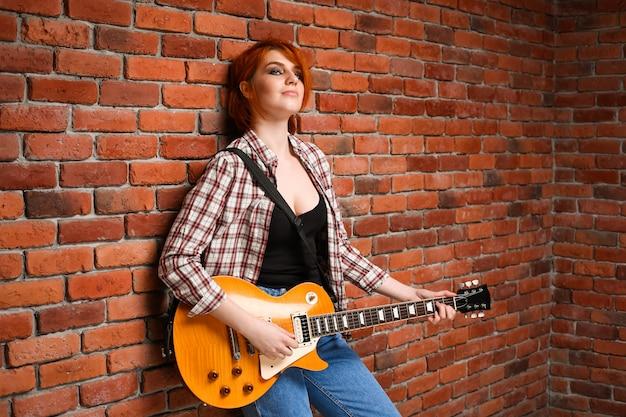 Portret van een jong meisje met gitaar op bakstenen achtergrond. Gratis Foto