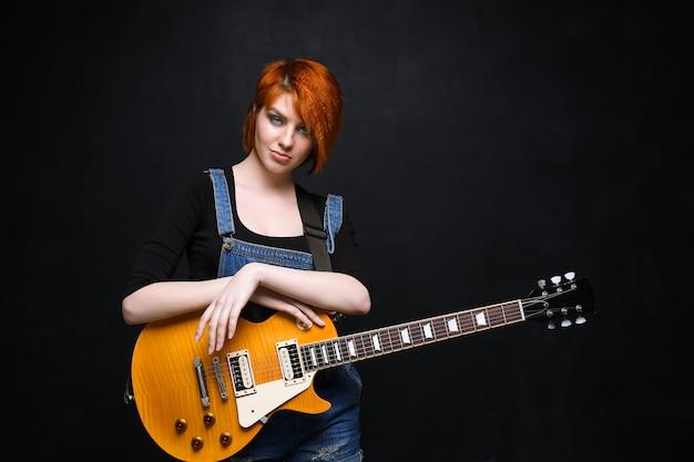 Portret van een jong meisje met gitaar op zwarte achtergrond. Gratis Foto