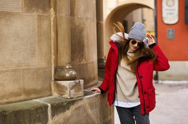 Portret van een jong modieus meisje die op de straat van de stad in de wintertijd lopen Premium Foto