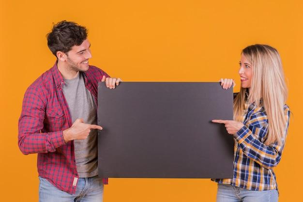 Portret van een jong paar dat hun vinger op leeg zwart aanplakbiljet richt tegen een oranje achtergrond Gratis Foto