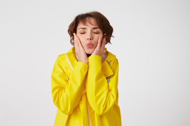 Portret van een jong schattig korthaar meisje draagt in gele regenjas, kus met gesloten ogen verzenden en wangen aanraakt, staat over witte muur. Gratis Foto