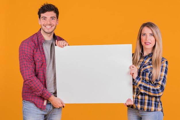 Portret van een jong stel presenteren witte plakkaat tegen een oranje achtergrond Gratis Foto