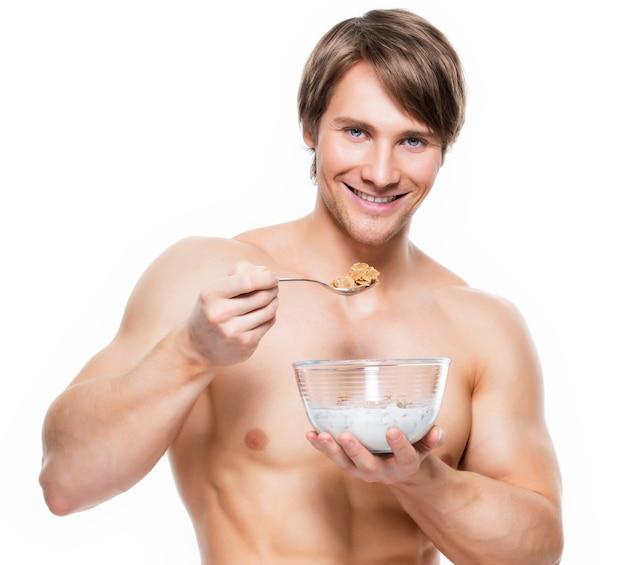 Portret van een jonge aantrekkelijke spiermens die vlokken met melk eet - die op witte muur wordt geïsoleerd. Gratis Foto
