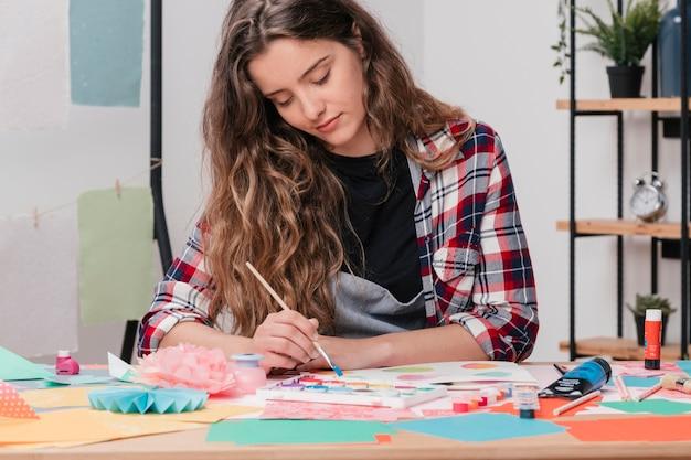 Portret van een jonge aantrekkelijke vrouwelijke kunstenaar die op papier schildert Gratis Foto