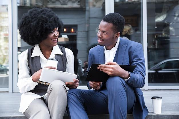 Portret van een jonge afrikaanse zakenman en een onderneemster die een bureauonderbreking nemen Gratis Foto