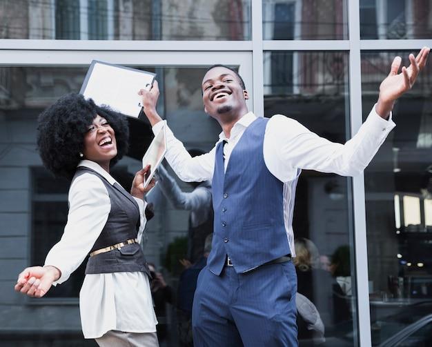 Portret van een jonge afrikaanse zakenman en een onderneemster die van het succes genieten Gratis Foto