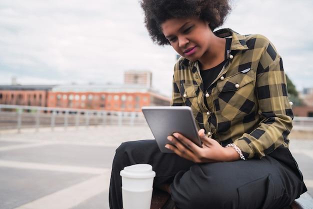 Portret van een jonge afro-amerikaanse latijns-vrouw met behulp van haar digitale tablet zittend op een bankje buitenshuis. technologie concept. Gratis Foto