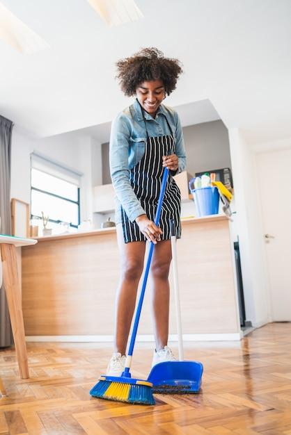 Portret van een jonge afrovrouw die houten vloer met bezem thuis vegen Premium Foto