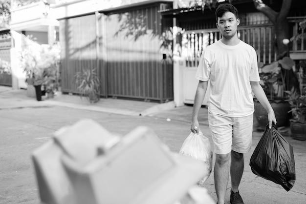 Portret van een jonge aziatische man die het huisvuil thuis neemt Premium Foto