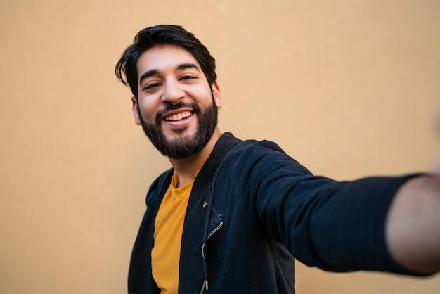 Portret van een jonge bebaarde hipster man camera kijken en het nemen van een selfie tegen geel. Gratis Foto