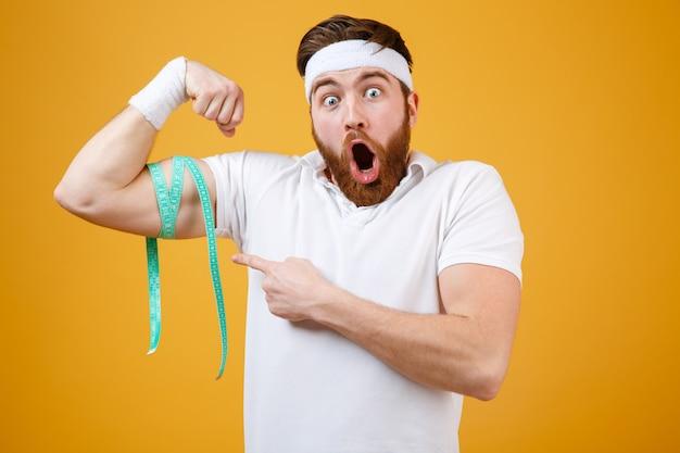 Portret van een jonge bebaarde opgewonden fitness man meten biceps Gratis Foto
