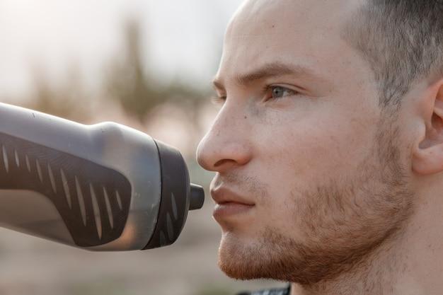 Portret van een jonge blanke man drinkwater uit een fles na of voor de training Premium Foto