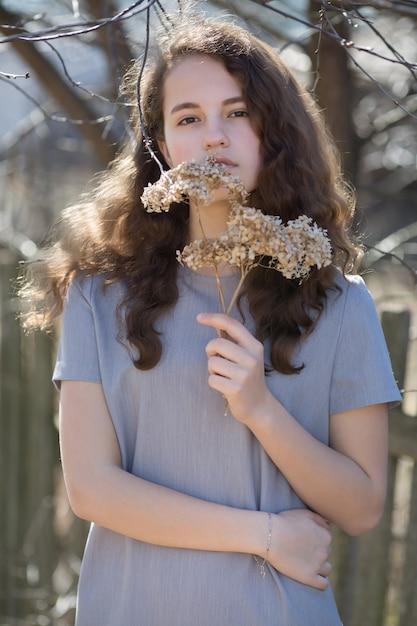 Portret van een jonge blanke vrouw. gelukkig mooi krullend meisjesclose-up, wind fladderend haar. lente portret buitenshuis. Premium Foto