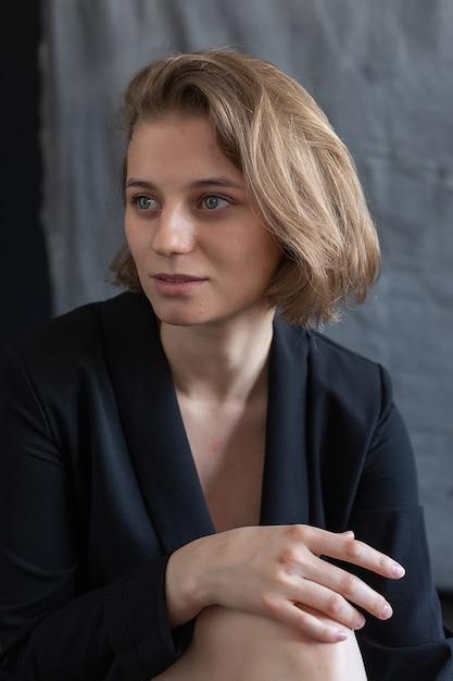 Portret van een jonge blanke vrouw met kort haar poseren in zwart pak jasje, grijze stof zit. mooi meisje glimlacht. kortharige aantrekkelijke vrouwelijke poses in de studio Premium Foto