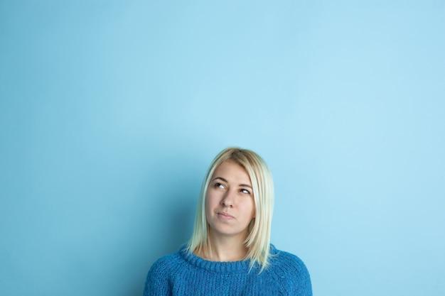 Portret van een jonge blanke vrouw ziet er dromerig, schattig en gelukkig uit. denken, benieuwd, dromen op blauwe studioachtergrond. copyspace voor uw advertentie. concept van toekomst, doel, dromen, visualisatie. Gratis Foto