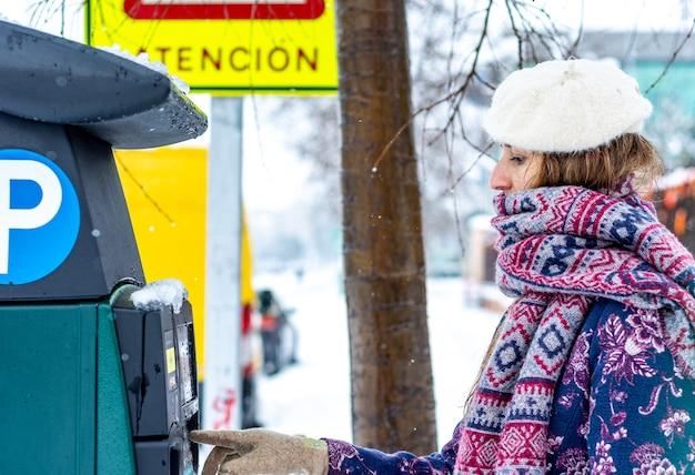 Portret van een jonge blonde vrouw gekleed in winterkleren krijgen een kaartje voor de parkeerautomaat op een besneeuwde laan in de stad. Premium Foto