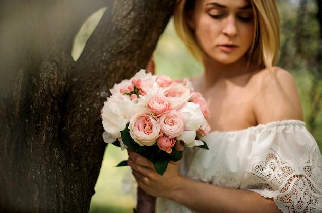Portret van een jonge blondevrouw met een boeket van bloemen die zich dichtbij de boom bevinden Premium Foto