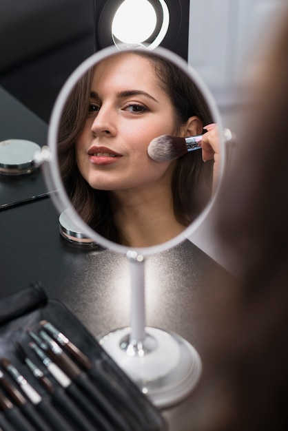 Portret van een jonge brunette die schoonheidsmiddelen toepast Gratis Foto